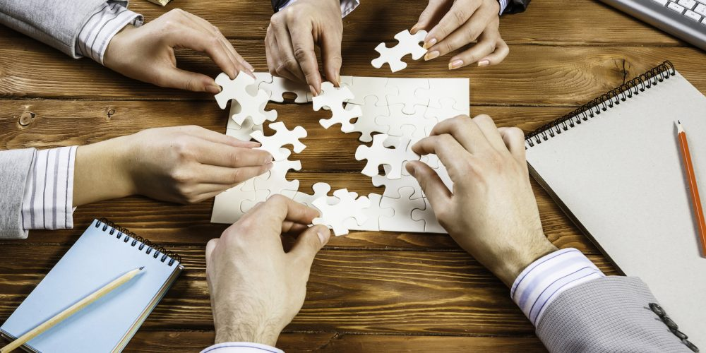 Group of business people sitting at table and assembling jigsaw puzzle